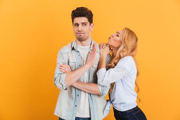 Portret młodego niezadowolonego mężczyzny gestykulującego, aby zatrzymać ręką, podczas gdy piękna kobieta całuje go w policzek, odizolowane na żółtej ścianie