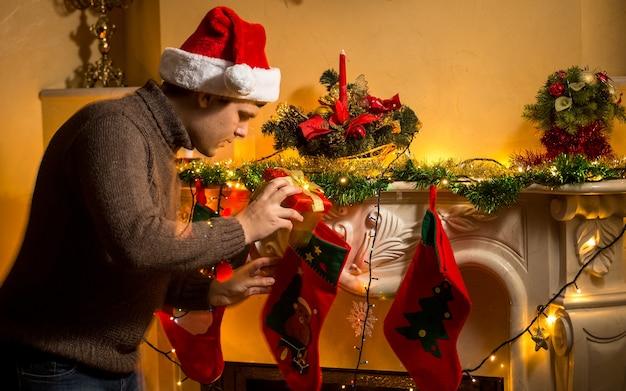 Portret młodego ojca wkładającego prezenty do świątecznych pończoch przy kominku