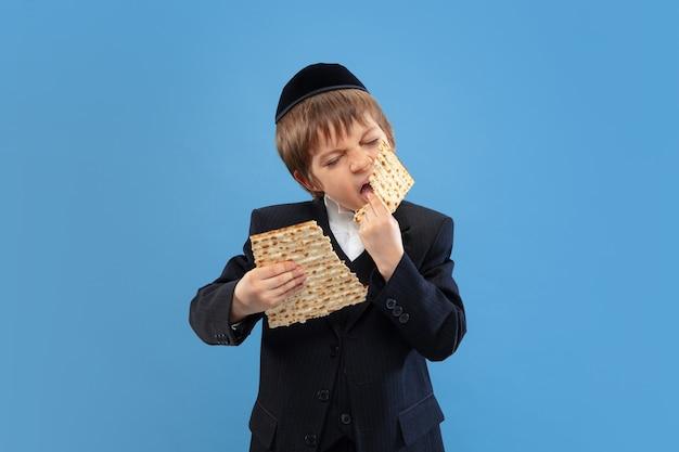 Portret młodego ortodoksyjnego chłopca żydowskiego na niebieskim ścianie spotkania paschy