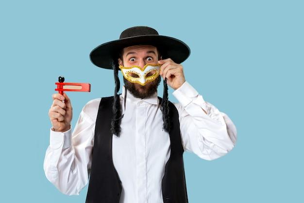 Portret młodego ortodoksyjnego żyda z drewnianą zapadką grager podczas festiwalu purim