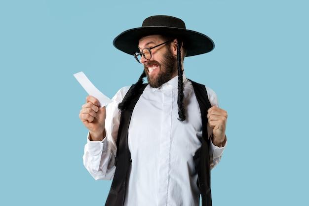 Portret młodego ortodoksyjnego żyda z kuponem zakładowym w studio.