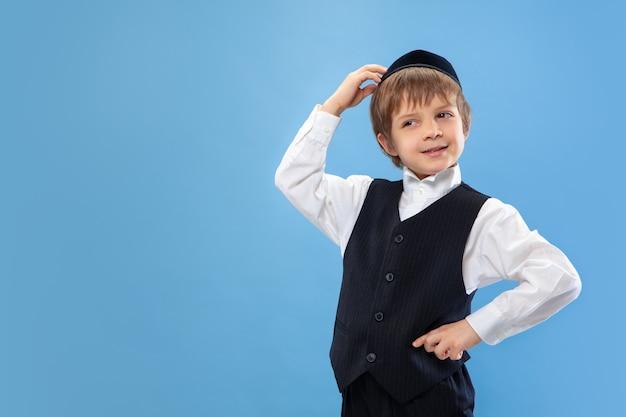 Portret młodego ortodoksyjnego żydowskiego chłopca izolowanego na niebieskiej ścianie studia