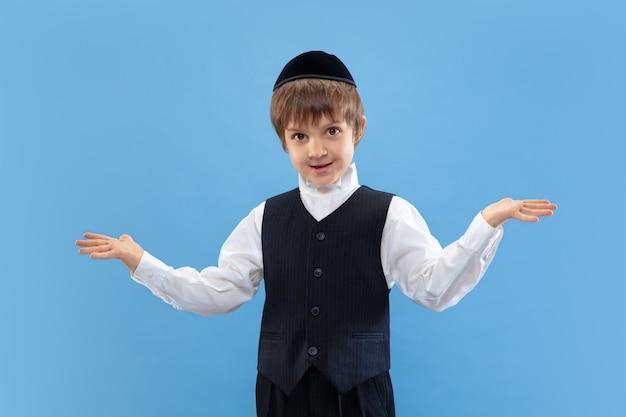 Portret młodego ortodoksyjnego żydowskiego chłopca na białym tle na niebieskim studio