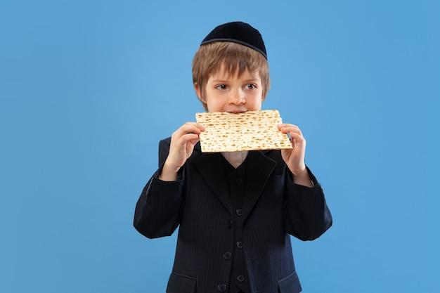 Portret młodego ortodoksyjnego żydowskiego chłopca na niebieskiej ścianie spełniającej paschę