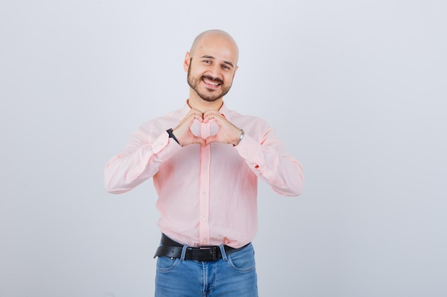 Portret młodego pewnego siebie mężczyzny pokazującego gest serca