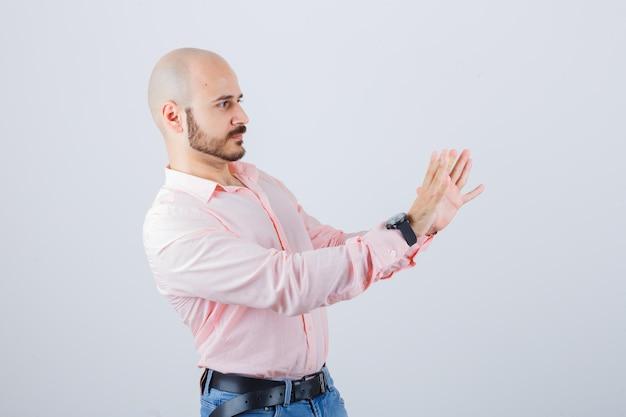 Portret młodego pewnego siebie mężczyzny pokazującego gest zatrzymania