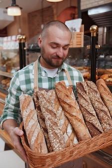 Portret młodego piekarza płci męskiej gospodarstwa świeżo upieczone bochenki chleba w koszu