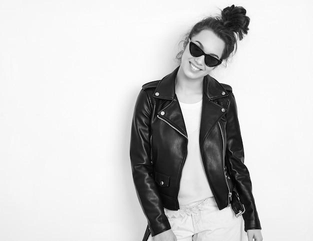 Portret młodego pięknego brunetki kobiety dziewczyny modela z nagim makeup jest ubranym lato modnisia rowerzysty skórzaną kurtkę odziewa w okularach przeciwsłonecznych pozuje blisko ściany.