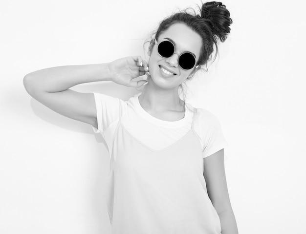 Portret młodego pięknego brunetki kobiety dziewczyny modela z nagim makeup w kolorowym lato menchii modnisiu odziewa w okularach przeciwsłonecznych pozuje blisko ściany. patrzeć szczęśliwie