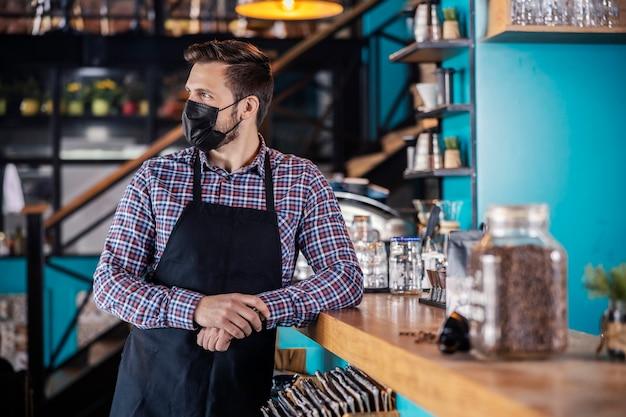Portret młodego pięknego mężczyzny w nowoczesnym mundurze stojącego z uśmiechem w kawiarni oparty o blat barowy