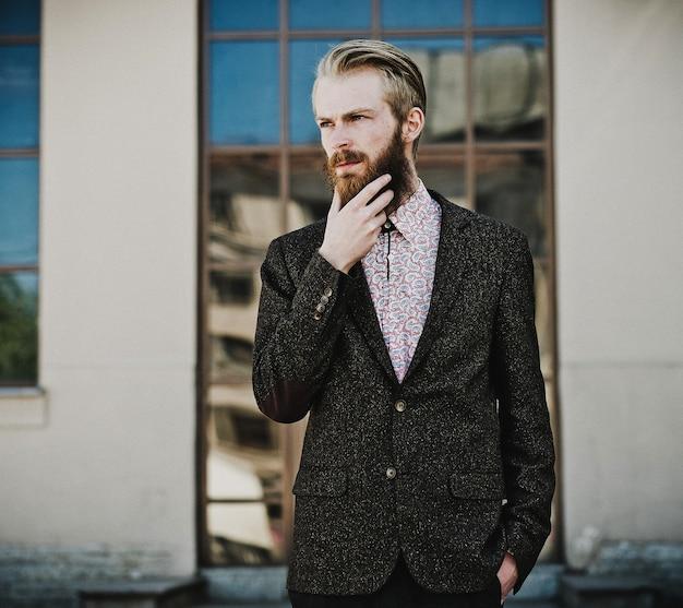 Portret młodego pięknego modnego mężczyzny na zewnątrz