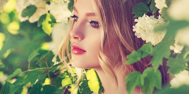 Portret młodego, pięknie wyglądającego modelu w cieniu świeżych zielonych drzew ogrodowych model z długą falującą fryzurą ubrany w elegancki makijaż kobiece piękno i kwiat młodości