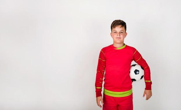 Portret młodego piłkarza w czerwonym mundurze stojącego z piłką nożną na białym tle z miejscem na tekst
