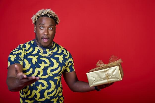 Portret młodego podekscytowanego afroamerykanina z prezentem w złotym opakowaniu w dłoni