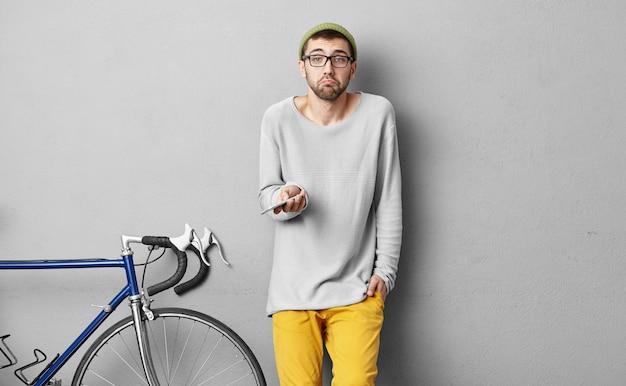 Portret młodego podróżnika, biorącego udział w wyścigu rowerowym, trzymającego w rękach nowoczesny smartfon, używającego nawigatora, próbującego znaleźć odpowiednią drogę, mającego wątpliwy wyraz twarzy, zagubionego w nieznanym miejscu