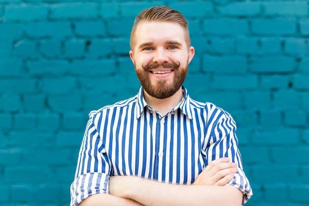 Portret młodego pozytywnego stylowego uśmiechniętego faceta z wąsami i brodą przed niebieskim brickwall