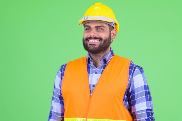 Portret młodego pracownika budowlanego z nadwagą brodaty mężczyzna indyjski przeciwko klucz chroma z zieloną ścianą