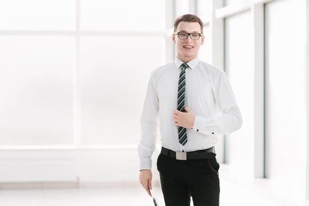 Portret młodego pracownika firmy stojącego w biurze. zdjęcie z miejscem na kopię
