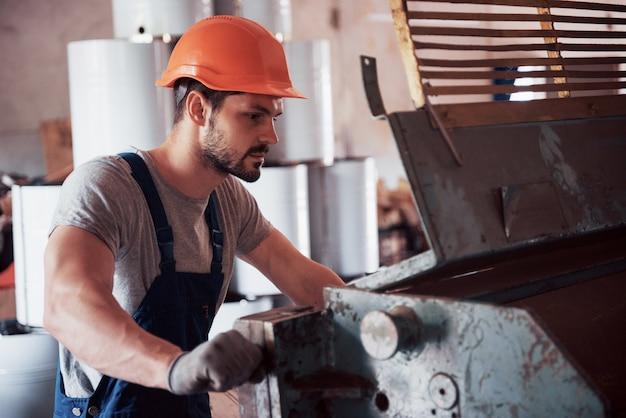 Portret młodego pracownika w kasku w dużej fabryce recyklingu odpadów.