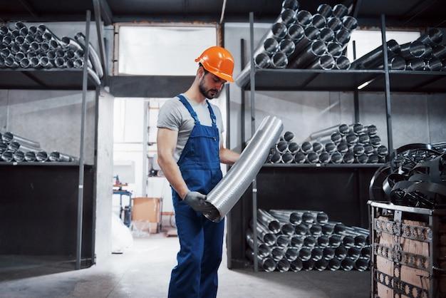 Portret młodego pracownika w kasku w dużym zakładzie obróbki metali.