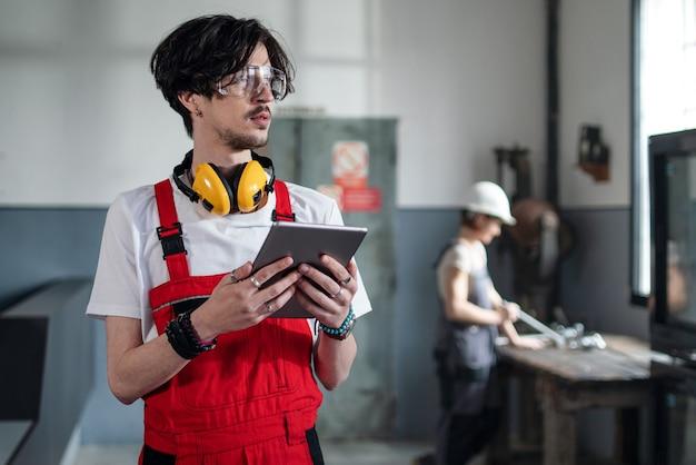 Portret młodego pracownika z kaskiem w pomieszczeniu w fabryce patrząc na kamery.