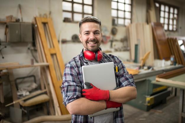 Portret młodego pracownika zawodowego z komputerem w warsztacie