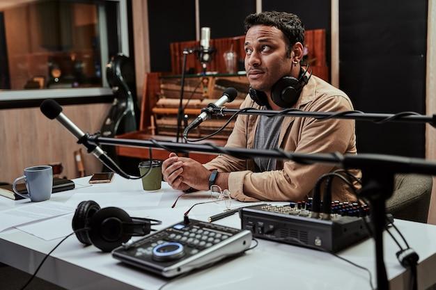 Portret młodego prezentera radiowego mężczyzny, który wygląda na skupionego, przygotowując się do moderowania programu na żywo w