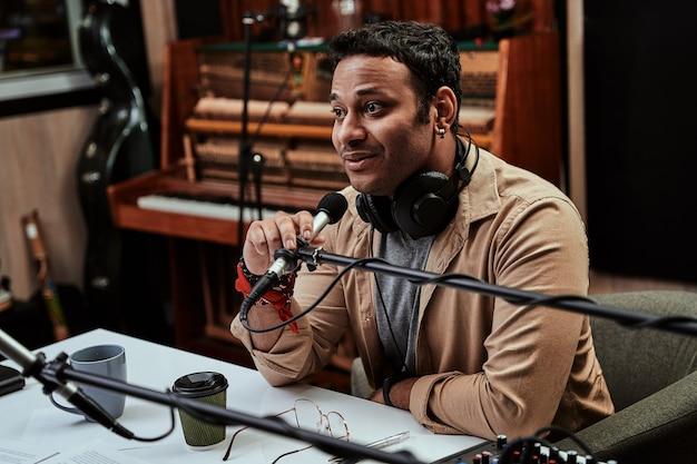 Portret młodego prezentera radiowego mężczyzny skupionego na rozmowie przez mikrofon moderującej transmisję na żywo