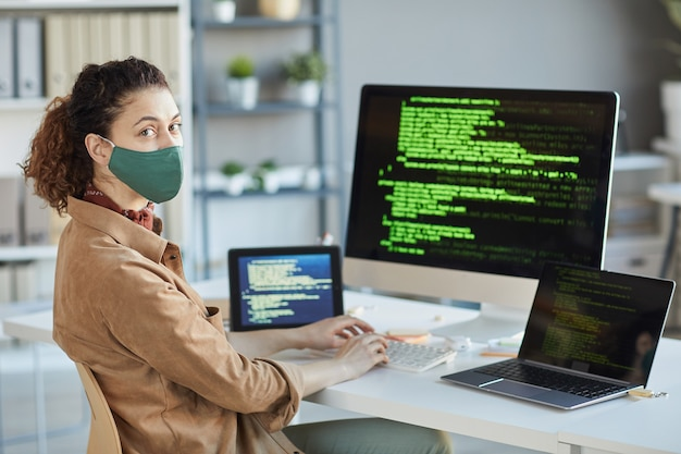 Portret młodego programisty w masce ochronnej patrząc z przodu siedząc w swoim miejscu pracy z komputerami na stole