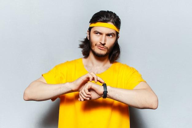 Portret młodego, przemyślanego i pewnego siebie mężczyzny w żółtej koszuli, za pomocą smartwatcha