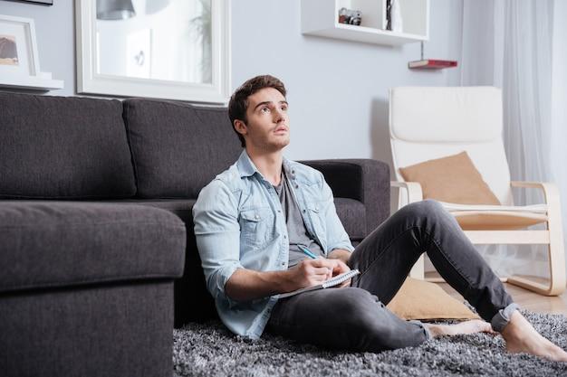 Portret młodego przypadkowego mężczyzny myślącego o czymś i robiącego notatki w zeszycie w domu