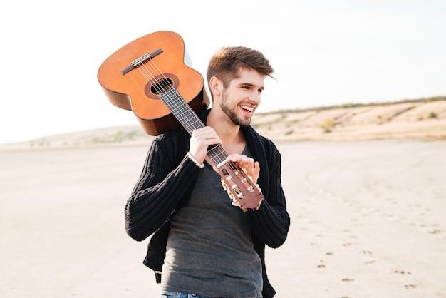 Portret młodego przypadkowego uśmiechniętego mężczyzny spacerującego po plaży i trzymającego gitarę na ramieniu