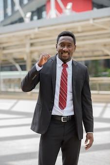 Portret młodego przystojnego afrykańskiego biznesmena w garniturze z widokiem na nowoczesny budynek w mieście na zewnątrz