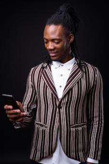 Portret młodego przystojnego afrykańskiego biznesmena z dredami na czarno