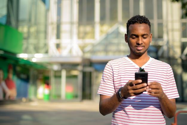 Portret młodego przystojnego afrykańskiego brodacza z afro włosami zwiedzania ulic miasta na świeżym powietrzu