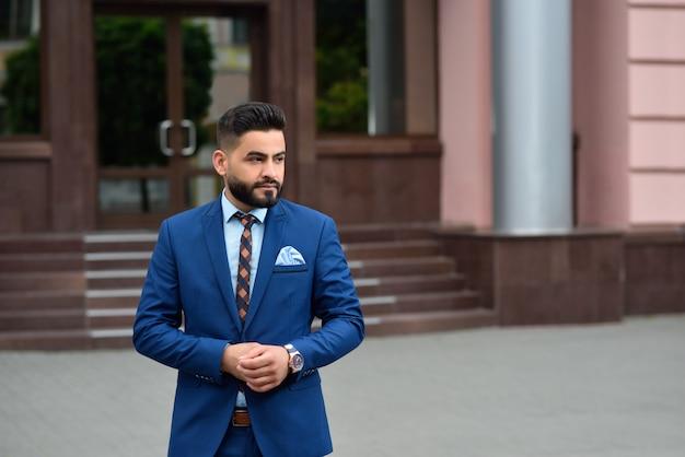 Portret młodego przystojnego biznesmena arabskiego, patrząc od hotelu w zamyśleniu, pozowanie na zewnątrz