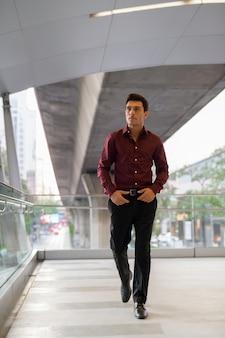 Portret młodego przystojnego biznesmena hiszpanie na kładce w mieście