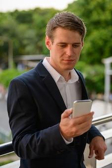 Portret młodego przystojnego biznesmena skandynawii o blond włosach na ulicach miasta na zewnątrz