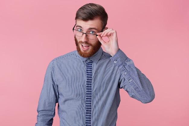 Portret młodego przystojnego brodacza, który opowiada zabawną historię, patrzy przez okulary na białym tle na różowym tle.