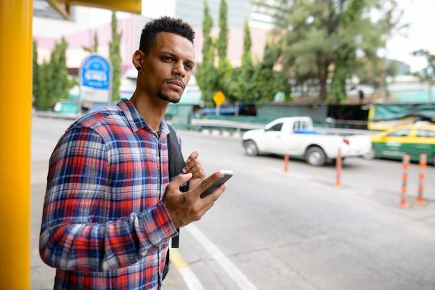 Portret młodego przystojnego, brodatego mężczyzny afrykańskiego hipster jako turysta z plecakiem czeka na przystanku autobusowym w mieście na świeżym powietrzu