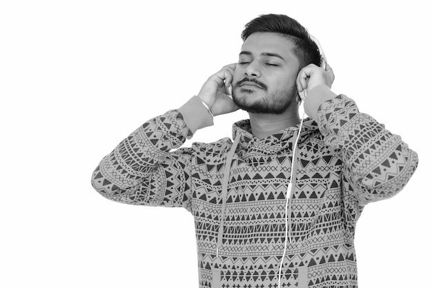Portret młodego przystojnego brodatego mężczyzny indyjskiego na białym w czerni i bieli