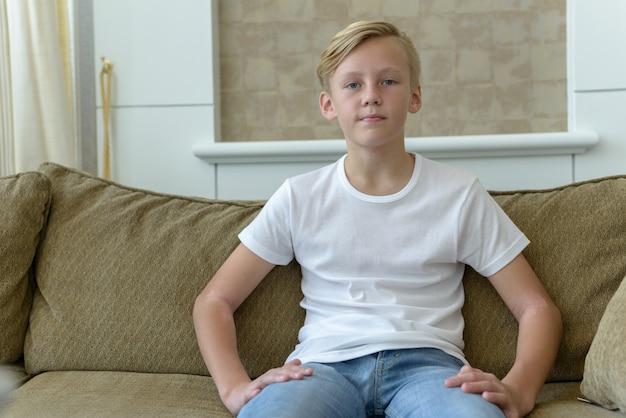 Portret młodego przystojnego chłopca skandynawii o blond włosach w salonie w domu