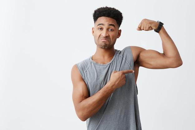 Portret młodego, przystojnego, ciemnoskórego mężczyzny z fryzurą afro w szarej koszuli bez rękawów przedstawiającej mięśnie, wskazując na nią z wyrazem pewności siebie.