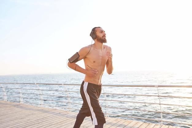 Portret młodego przystojnego faceta sportowego z brodą, biegnącego nad morzem, posłuchaj ulubionej mieszanki na słuchawkach. ciesz się porankiem i żartem.