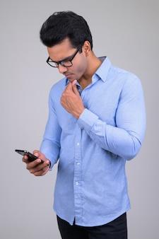 Portret młodego przystojnego indyjskiego biznesmena na białym tle