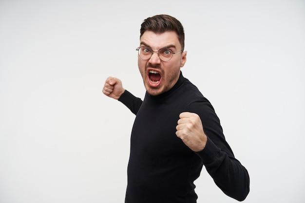 Portret młodego przystojnego, krótkowłosego brodatego faceta w okularach, podnoszącego pięści i krzyczącego z szeroko otwartymi ustami, na białym tle