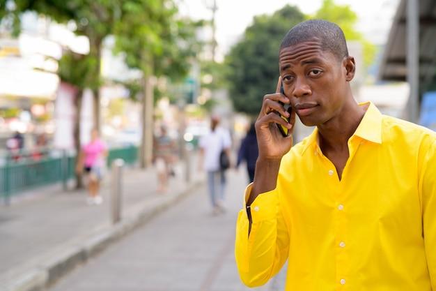 Portret młodego przystojnego łysego afrykańskiego biznesmena zwiedzania ulic bangkoku