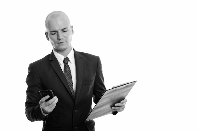 Portret młodego przystojnego łysego biznesmena w garniturze na białym tle w czerni i bieli
