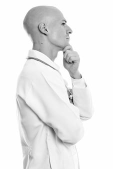 Portret młodego przystojnego łysego lekarza na białym tle w czerni i bieli