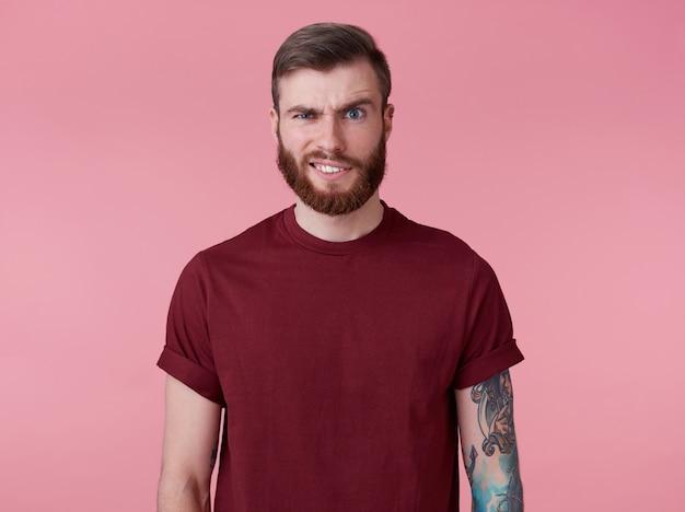 Portret młodego przystojnego marszczącego brwi niezrozumienie rudy brodaty mężczyzna w czerwonej koszulce, stoi na różowym tle patrzy w kamerę z obrzydzeniem.